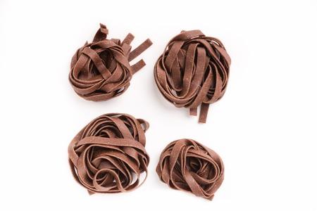 Raw unprepared chocolate tagliatelle nests isolated on white background. Unusual sweet Italian pasta dessert