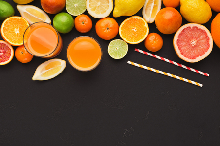 Border of assorted citruses on black background, copy space. Top view on oranges, lemons, tangerines and juice glasses, flat lay. Making detox freshes concept and recipe mockup