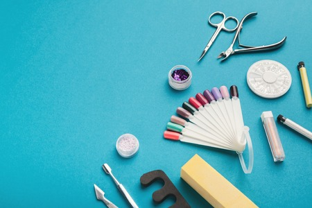 Manicure and pedicure beauty accessories on blue background, copy space. Nail polish samples, scissors, clippers and other supplies for home and salon procedure