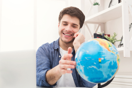 Young happy man playing with globe and talking on phone at home. Handsome guy preparing for vacation, consulting with agent, planning route of trip, booking hotel, copy space
