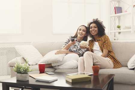 Smiling female friends relaxing and watching TV at home, eating popcorn, having rest after hard week, copy space