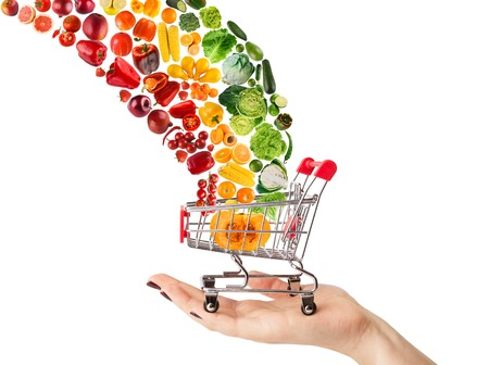 Female hand holding grocery cart with vegetables and fruits falling in it isolated on white. Healthy meals shopping, cornucopia and wellbeing concept. Collage of brignt food and trolley, cutout Stock Photo