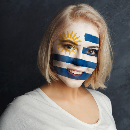 Face of young happy woman painted with flag of Uruguay. Football or soccer team fan, sport event, faceart and patriotism concept. Studio shot at gray background, copy space