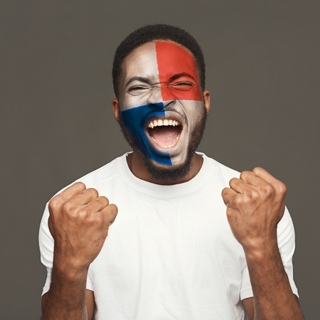 Face of young african-american unhappy man painted with flag of Panama. Football or soccer team fan, sport event, faceart and patriotism concept. Studio shot at gray background, copy space