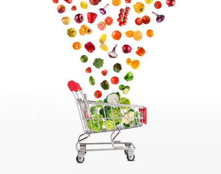 Grocery cart with vegetables and fruits falling in it isolated on white. Healthy meals shopping, cornucopia and wellbeing concept. Collage of brignt food and trolley, cutout