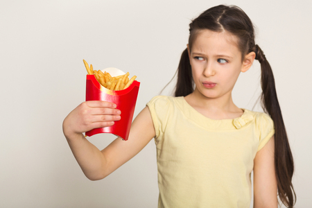 Disgusted little girl holding a bag of fries isolated on white background. Fast food against healthy food concept, copy space, selective focus Stock Photo