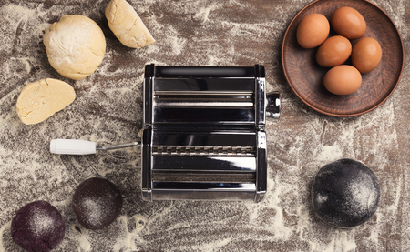 Pasta machine, eggs and raw colorful dough on floured kitchen table, top view. Preparation of homemade italian fettuccine, copy space