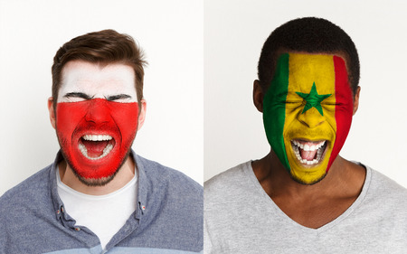 Emotional soccer fans with painted Poland and Senegal flags on faces. Confrontation of football team supporters from rival countries, sport event, faceart and patriotism concept. 写真素材