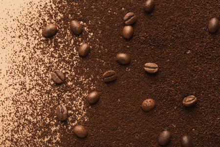 Roasted coffee beans scattered over heap of ground seeds, copy space. Coffee shop advertisement and textured background