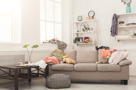 Sofa in messy living room with many stack of clothes. Disorder and mess at home, copy space 스톡 콘텐츠