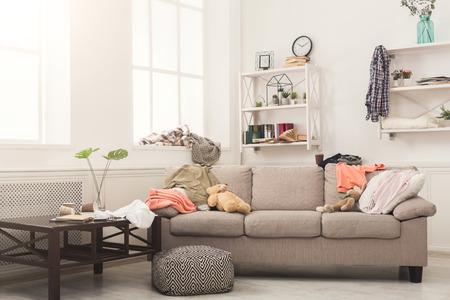 Sofá en la sala de estar desordenada con mucha pila de ropa. Desorden y desorden en casa, espacio de copia