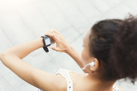 Young african-american woman using smart watch, girl preparing for jogging, copy space, over shoulder shot