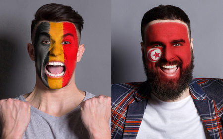 Emotional soccer fans with painted Belgium and Tunisia flags on faces. Confrontation of football team supporters from rival countries, sport event, faceart and patriotism concept.