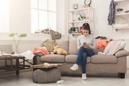 Wanhopige hulpeloze vrouw zittend op de Bank in rommelige woonkamer. en chatten op mobiel, omringd door veel stapels kleren. Wanorde en rommel thuis, kopieer ruimte