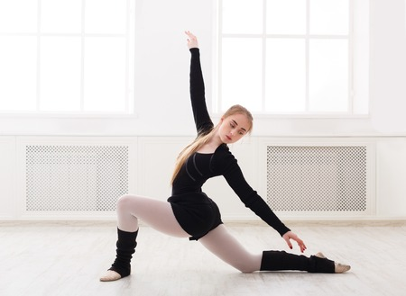 Beautiful graceful ballerina in black stretching in white classroom interior. Ballet class training, copy space