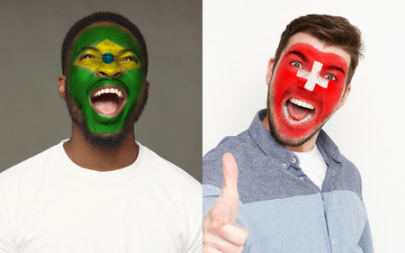 Emotional soccer fans with painted Brazil and Switzerland flags on faces. Confrontation of football team supporters from rival countries, sport event, faceart and patriotism concept. 免版税图像
