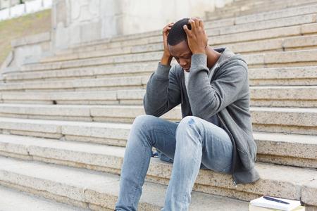 Destacó el hombre afroamericano sentado solo con dolor de cabeza en la universidad en las escaleras. Chico estudiante negro deprimido reprobó los exámenes, expulsado de la universidad, espacio de copia