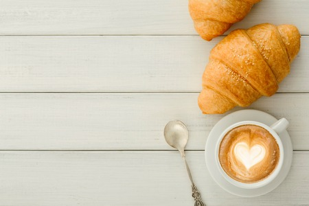 Tasty reakfast background. Hot foamy coffee and fresh croissants on wooden table, top view, copy space. Delicious start of the day and bakery concept Banco de Imagens