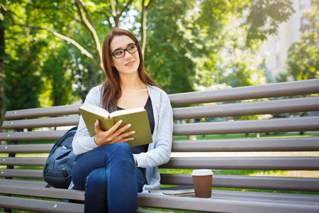 Smiling young woman in glasses, sitting on a bench in the park. Brunette girl relaxing and reading a book. Lifestyle and chiling concept Reklamní fotografie