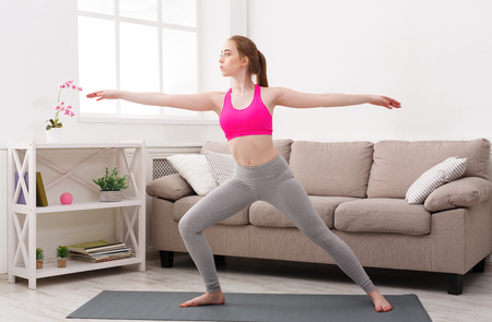 Fitness, woman yoga relax meditation in warrior pose at home. Young slim girl makes exercise.