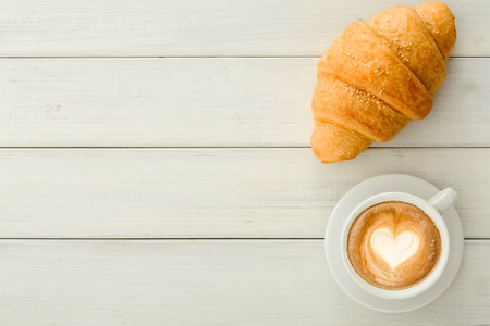 Tasty reakfast background. Hot foamy coffee and fresh croissants on wooden table, top view, copy space. Delicious start of the day and bakery concept 스톡 콘텐츠