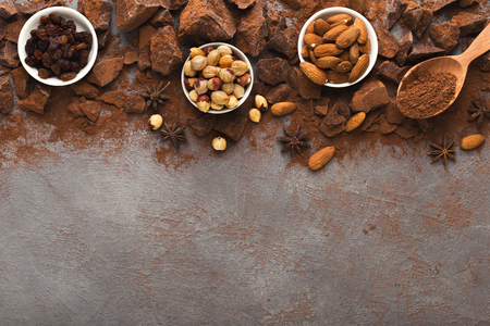 Chocolate chunks on gray background, cocoa powder and variety of nuts and spices bowls, top view. Confectionery shop advertising and cooking ingredients concept, copy space, mockup for recipe