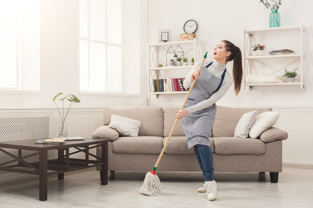 Happy woman in uniform cleaning home, singing at mop like at microphone and having fun, copy space. Housework, chores concept