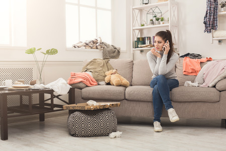 Desperate helpless woman sitting on sofa in messy living room. and talking on mobile, surrounded by many stack of clothes. Disorder and mess at home, copy space
