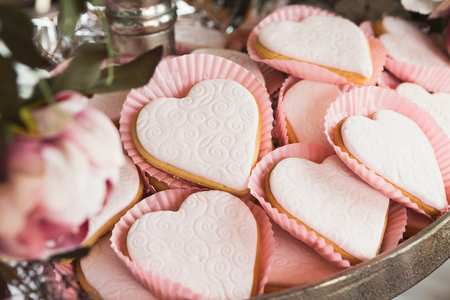Closeup of heart shaped cookies with pink textured icing on silver tray. Baked snaks for party dessert stand. Candy bar and catering concept for birthday, wedding and other holiday celebration