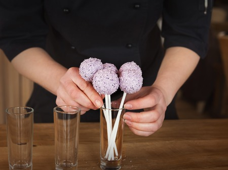 Waitress arranging candy bar. Putting cake pops with pink icing into glasses, closeup. Dessert table and catering concept for party, birthday, wedding and other holiday celebration