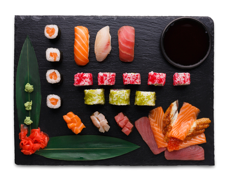 Sushi set on black slate isolated on white background. Rolls and sashimi with salmon, tuna and vegetables, top view, cutout. Japanese cuisine