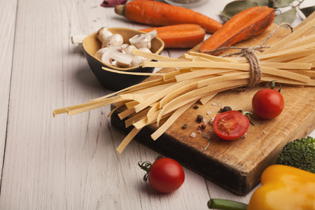 Raw handmade tagliatelle and various vegetables on white wooden table. Cooking pasta background