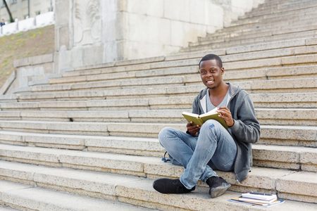Young smiling african-american man reading book, sitting on campus stairs, studying and preparing for exams at university or college. Education concept, copy space