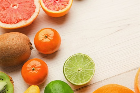 Closeup of citruses assortment and glass of orange juice on white wooden background. Detox, breakfast and healthy lifestyle concept