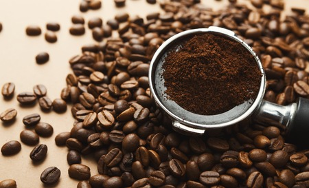 Filter holder with ground coffee and roasted beans scattered around on beige background, closeup Stock Photo