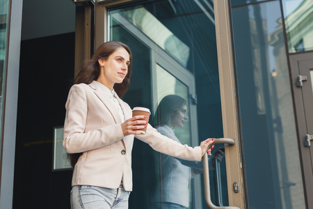 Happy confident businesswoman walking out of modern office center, drinking take away coffee, copy space