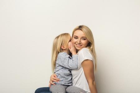 愉快的母亲和小女儿画象白色演播室背景的。逗人喜爱的孩子在她的妈妈耳朵耳语秘密。信任,保密,护理和支持,母亲节贺卡样机,副本空间vwin202