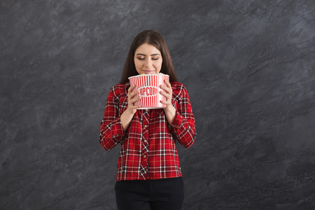 Happy beautiful young girl smelling popcorn with closed eyes, while watching film on grey background Фото со стока