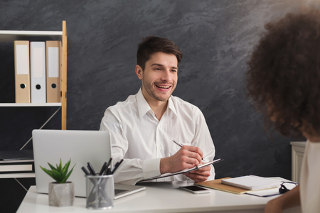 Couple of young colleagues working in modern office. Cheerful man hr interviewing female candidate, copy space Stock Photo