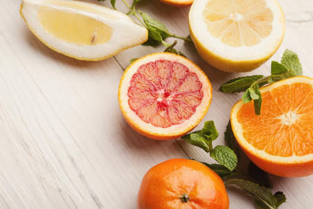Closeup of citruses assortment on white wooden background. Detox, breakfast and healthy lifestyle concept, copy space