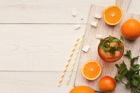 Closeup of citruses assortment and glass of orange juice on white wooden background. Detox, breakfast and healthy lifestyle concept, top view, copy space