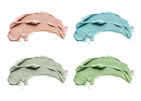 Set cosmetische uitstrijkjes van het moddermasker geïsoleerd op een witte achtergrond. Bovenaanzicht, close-up textuur van blauwe, rode en groene gezichtsklei, kopie ruimte Stockfoto