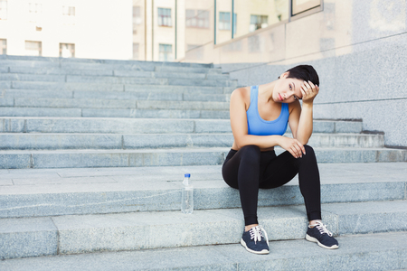 Tired woman runner is having break, sitting on steps outdoors. City jogging and active lifestyle concept, copy space Stock Photo