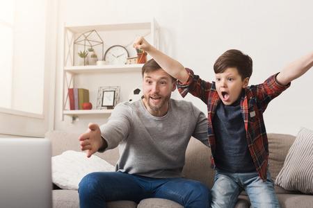 Padre e hijo viendo fútbol en la televisión en casa. Hombre emocional y niño animando a su equipo favorito, entusiasmo familiar, espacio de copia