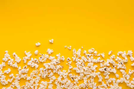 Border of popcorn scattered over yellow background with copy space, top view. Minimalistic design for movie poster, entertainment concept