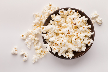 Wooden rustic bowl of popcorn isolated on white background, top view. Fast food, cinema snack and entertainment concept, cutout Foto de archivo