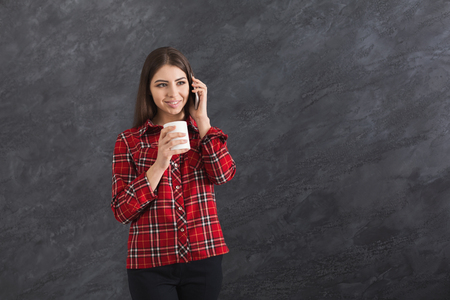 Beautiful and young happy caucasian woman talking on smartphone and drinking coffee on grey background, copy space Фото со стока