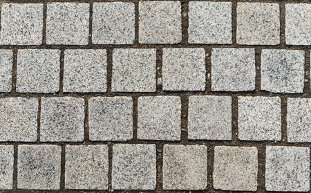 Stone pavement texture, granite cobbles background. Adstract backdrop