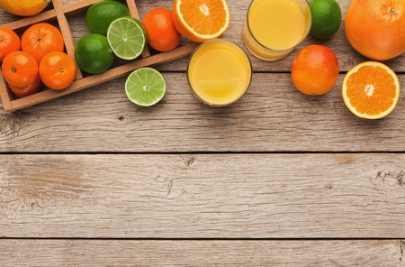 Frame with assortment of citruses on rustic wooden background, copy space. Top view on oranges, lemons, tangerines and other exotic fruits, flat lay Stock Photo