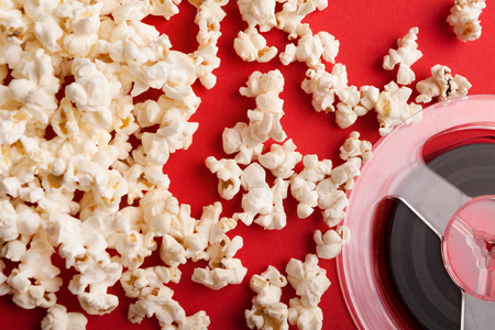 Movie background. Popcorn and film reel on red backdrop Entertainment and cinematography concept Stock Photo